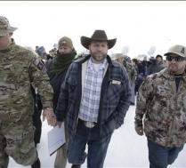 Ammon Bundy, center, one of the sons of Nevada rancher Cliven Bundy, walks off after speaking with reporters during a news conference at Malheur National Wildlife Refuge headquarters Monday, Jan. 4, 2016, near Burns, Ore.