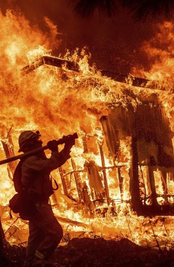Firefighter Jose Corona sprays water as flames from the Camp Fire consume a home in Magalia, California, Nov. 9, 2018. (AP Photo/Noah Berger)
