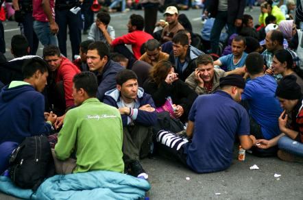 Migrants rest after arriving at the border between Austria and Hungary near Heiligenkreuz, about 110 miles south of Vienna, Austria, Monday, Sept. 14, 2015.