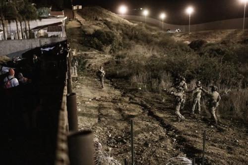 U.S. Border Patrol officers point their weapons at migrants as they prepared to cross the border fence to get into the U.S. from Tijuana, Mexico, Jan. 1, 2019. (AP Photo/Daniel Ochoa de Olza)