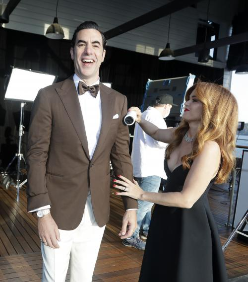 Isla Fisher helps make the final touches to clean the suit of Sacha Baron Cohen as they arrive to attend a screening of the Oscars, April 26, 2021 in Sydney, Australia. (AP Photo/Rick Rycroft, Pool)