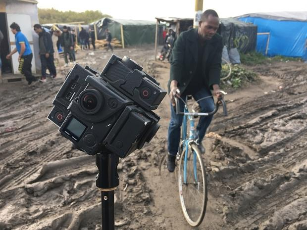 """A man rides a bike past a special rig designed to capture 360 imagery for use in virtual reality storytelling using go-pro cameras during filming of """"Seeking Home: Life in the Calais Migrant Camp,"""" AP's first virtual reality video report."""