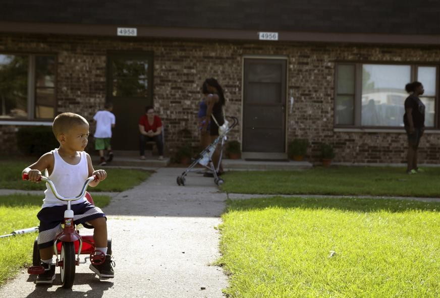 In this Aug. 3, 2016 file photo, Joseph Russell, 2, rides his tricycle outside his home at the West Calumet Housing Complex in East Chicago, Ind.