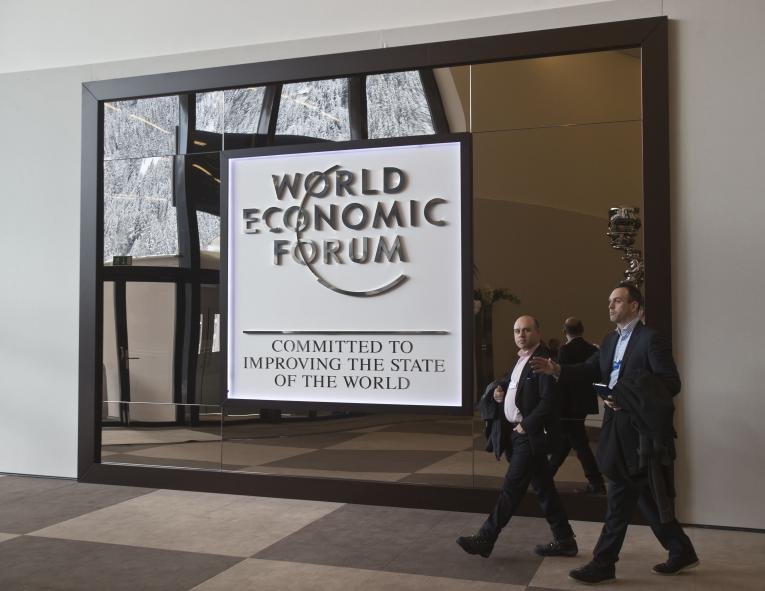 Participants walk in the main entrance hall of the Congress Center