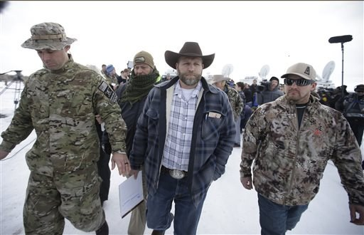 Ammon Bundy, center, one of the sons of Nevada rancher Cliven Bundy, walks off after speaking with reporters during a news conference at Malheur National Wildlife Refuge headquarters Monday, Jan. 4, 2016, near Burns, Ore. (AP Photo/Rick Bowmer)