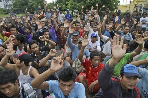 Rescued Burmese fishermen raise their hands as they are asked who among them wants to go home at the compound of Pusaka Benjina Resources fishing company in Benjina, Aru Islands, Indonesia, April 3, 2015. (AP Photo/Dita Alangkara)