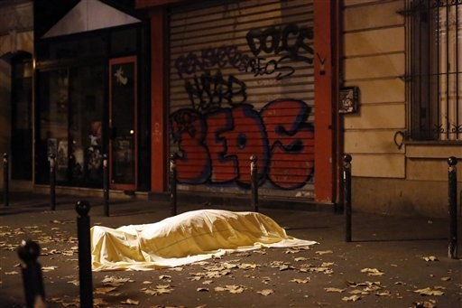 A victim of an attack in Paris lies dead outside the Bataclan theater, Friday Nov. 13, 2015.