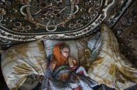 Natalya Vetrova sleeps holding a bottle with fresh cow milk at home in Zalyshany, 53 km (32 miles) southwest of the destroyed reactor of the Chernobyl plant, Ukraine. (AP Photo/Mstyslav Chernov)