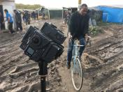 "A man rides a bike past a special rig designed to capture 360 imagery for use in virtual reality storytelling using go-pro cameras during filming of ""Seeking Home: Life in the Calais Migrant Camp,"" AP's first virtual reality video report."