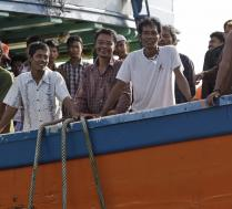 Recently rescued Burmese fishermen smile on their boat upon arrival in Tual, Indonesia, April 4, 2015. (AP Photo/Dita Alangkara)