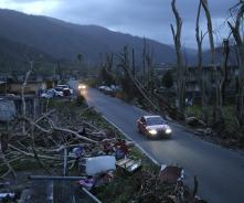 Neighbors sit on a couch outside their destroyed homes as the sun sets in the aftermath of Hurricane Maria, in Yabucoa, Puerto Rico, Sept. 26, 2017. (AP Photo/Gerald Herbert)