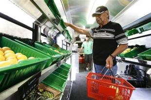 In this Wednesday, July 15, 2015 photo, Pablo Salazar shops for fruits and vegetables in the Fresh Stop bus, a mobile market, at the Taft Community Center, in Orlando, Fla.