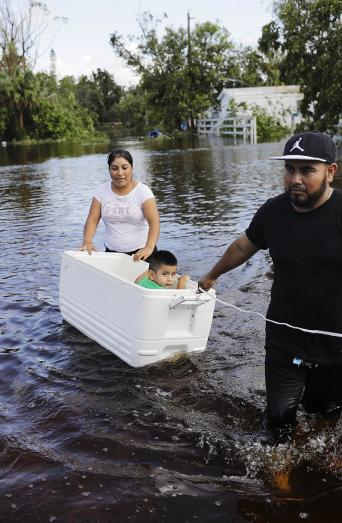 Alfonso Jose pulls his son in a cooler as he and his wife wade through their flooded street in Bonita Springs, Florida, to reach an open convenience store in the wake of Hurricane Irma, Sept. 12, 2017. (AP Photo/David Goldman)