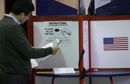 A voter examines a ballot at an early voting location in Worcester, Massachusetts, Oct. 24, 2016. (AP Photo/Steven Senne)
