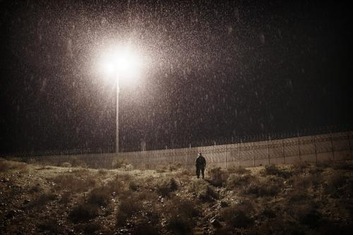 A U.S. Border Protection officer stands under the rain as he watches the border fence between the U.S. side and San Diego, California, from Tijuana, Mexico, Jan. 1, 2019. (AP Photo/Daniel Ochoa de Olza)