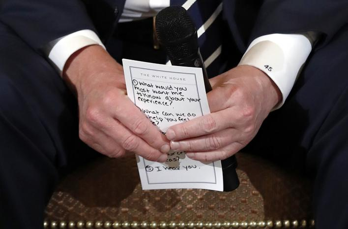 President Donald Trump holds notes during a listening session with high school students and teachers in the State Dining Room of the White House in Washington, Feb. 21, 2018. (AP Photo/Carolyn Kaster)